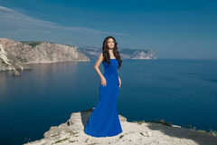 Fashion Happy beautiful woman in long dress over blue sky, outdo Stock Photo