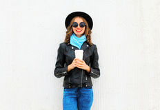 Fashion happy cool girl with coffee cup wearing black rock jacket, hat over white Stock Image