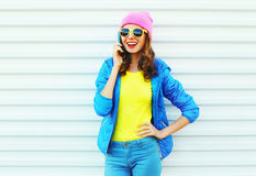 Fashion happy cool smiling girl talking on smartphone in colorful clothes over white background wearing pink hat yellow sunglasses Royalty Free Stock Photography