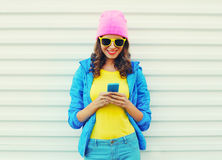 Fashion happy cool smiling girl using smartphone in colorful clothes over white background wearing pink hat yellow sunglasses royalty free stock image