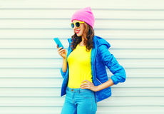 Fashion happy cool smiling girl using smartphone in colorful clothes over white background wearing a pink hat yellow sunglasses Royalty Free Stock Photos