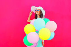 Fashion happy pretty smiling woman with an air colorful balloons is having fun in summer over a pink background Stock Photo