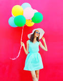 Fashion happy pretty smiling woman with an air colorful balloons is having fun in summer on pink background. Fashion happy pretty smiling woman with an air Royalty Free Stock Photos