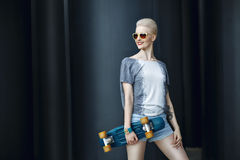 Fashion happy smiling hipster cool girl in sunglasses with skateboard behind the black urban background. Royalty Free Stock Image