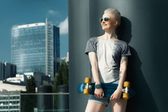 Fashion happy smiling hipster cool girl in sunglasses with skateboard behind the city urban outdoor background. Stock Photos