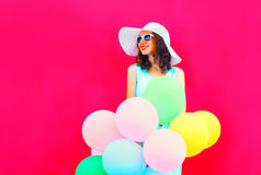 Fashion happy smiling young woman with an air colorful balloons is having fun on pink background Stock Images