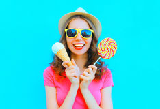 Fashion happy smiling young woman with ice cream and lollipop over colorful blue. Background Stock Image