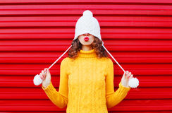 Fashion happy woman blowing red lips makes air kiss wearing colorful knitted hat, yellow sweater over red Stock Photos