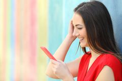 Fashion happy woman checking smart phone outside stock photography