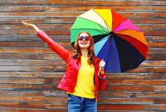 Fashion happy woman with colorful umbrella in autumn day over wooden background wearing red leather jacket Stock Image