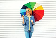Fashion happy woman laughing with colorful umbrella, holds smartphone. On white background in city royalty free stock photography