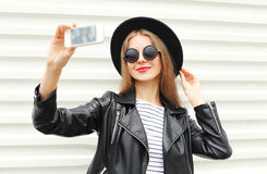 Fashion happy woman makes self portrait on smartphone in black rock style over city white Royalty Free Stock Image