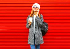 Fashion happy woman talks on a smartphone holds coffee cup on a red. Background Royalty Free Stock Image
