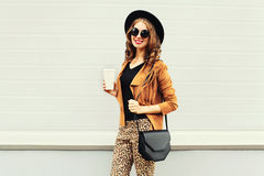 Fashion happy young smiling woman with coffee cup wearing a retro elegant hat, sunglasses, brown jacket and black handbag Royalty Free Stock Image