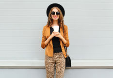 Fashion happy young smiling woman with coffee cup wearing retro elegant hat, sunglasses, brown jacket and black handbag Stock Photos