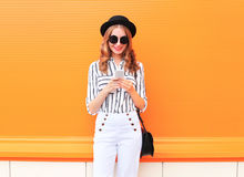 Fashion happy young smiling woman model using smartphone wearing a black hat white pants over colorful orange Royalty Free Stock Images