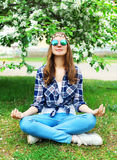 Fashion hippie woman sitting relaxes in yoga pose lotus on grass Royalty Free Stock Photography