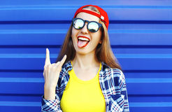 Fashion hipster cool girl in sunglasses and colorful clothes having. Portrait of fashion hipster cool girl in sunglasses and colorful clothes having fun over Stock Photo