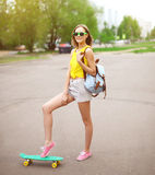Fashion hipster cool girl in sunglasses with skateboard Royalty Free Stock Photo