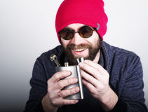 Fashion hipster cool man in sunglasses and colorful clothes pours himself a drink from a metal flask Stock Photography
