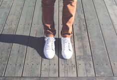 Fashion hipster cool man with white sneakers close-up stands. On wooden floor stock images