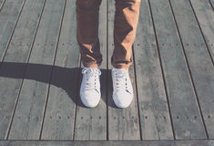 Fashion hipster cool man with white sneakers, soft vintage toned. Colors stock images