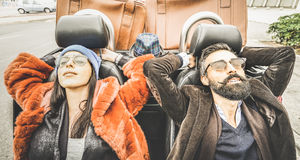 Fashion hipster couple relaxing at car trip on the road. Fashion hipster boyfriend and girlfriend - Happy couple relaxing together at car trip - Modern love stock image