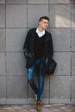 Fashion hipster male model posing outdoor. Fashion hipster male model posing and holding a bag posing outdoor Royalty Free Stock Photography