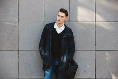 Fashion hipster male model posing outdoor. Fashion hipster male model posing and holding a bag posing outdoor Royalty Free Stock Photos