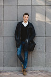 Fashion hipster male model posing outdoor. Fashion hipster male model posing and holding a bag posing outdoor Stock Photo