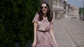 Fashion hipster style girl walks through the summer city streets. In floral pattern color dress and dark sunglasses stock footage