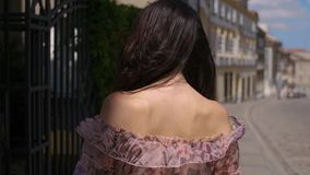 Fashion hipster style girl walks through the summer city streets. In floral pattern color dress and dark sunglasses stock video footage