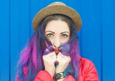 Fashion hipster woman with colorful hair having fun. Over blue background Stock Photo