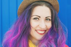 Fashion hipster woman with colorful hair having fun. Over blue background Stock Photos