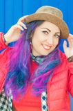 Fashion hipster woman with colorful hair having fun. Over blue background Royalty Free Stock Image
