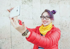 Fashion hipster woman with colorful hair taking picture of herse. Lf over wall background Stock Image