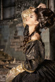 Fashion history. Art Fashion. Beautiful young woman in elegant historical dress and with barocco updo hairstyle posing in the ruins of the castle. Renaissance Royalty Free Stock Images