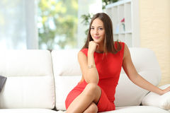 Fashion housewife woman posing at home. Fashion housewife woman in red posing on a couch at home and looking at camera royalty free stock image