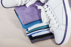 Fashion Ideas and Concepts. Pair of White Fasionable Sneakers Cl. Ose to Stack of Prepared Clothing. Horizontal Image Stock Photo