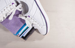 Fashion Ideas and Concepts. Pair of White Fasionable Sneakers Cl. Ose to Stack of Prepared Clothing. Horizontal Image with Copy Space Royalty Free Stock Images