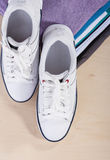 Fashion Ideas and Concepts. Pair of White Fasionable Sneakers Cl. Ose to Stack of Prepared Clothing. Vertical Image Composition Stock Photo