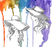 Fashion illustration. Girls in hats on a watercolor background Royalty Free Stock Image