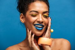 Fashion image of smiling mulatto woman with colorful makeup and. Curly hair in bun touching her pretty face and looking on camera isolated over blue wall Royalty Free Stock Photos