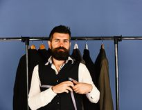 Fashion and individual style concept. Man with beard by clothes rack. Tailor with serious face. Holds measuring tape near custom jackets on blue background stock images