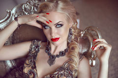 Fashion indoor portrait of beautiful sensual blond woman with ma Royalty Free Stock Image