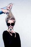 Fashion inspired image of womans haircut. Fashion inspired image of a young woman with sunglasses and huge ring, not paying attention to a male hairdressers hand Royalty Free Stock Photo
