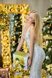 Fashion interior photo of beautiful gorgeous woman lady with blond hair in luxurious dress posing in room with Christmas tree and Stock Photo