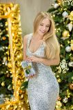 Fashion interior photo of beautiful gorgeous woman lady with blond hair in luxurious dress posing in room with Christmas tree and Royalty Free Stock Images