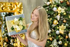 Fashion interior photo of beautiful gorgeous woman lady with blond hair in luxurious dress posing in room with Christmas tree and Royalty Free Stock Photos
