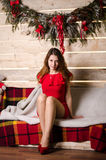 Fashion interior photo of beautiful girls with blond hair wear luxurious party dresses and Santa hats,holding glasses with ch Royalty Free Stock Photography
